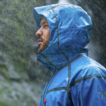 コロンビアのレインウェアを着て雨に打たれる男性