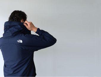 ノースフェイスのジャケットのフードをかぶる人
