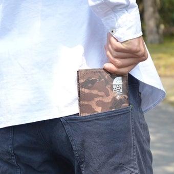 ノースフェイスの財布をポケットから取り出す男性