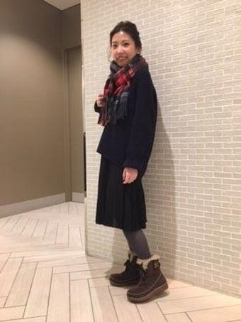 ソレルのブーツを履いたコートを着た女性
