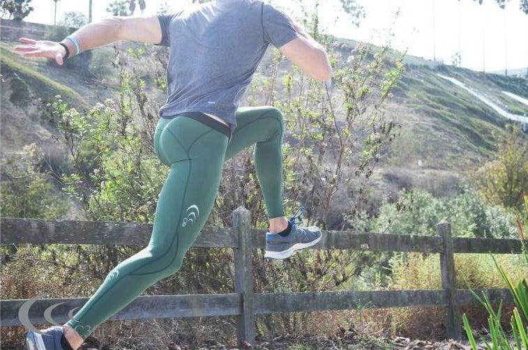 緑色のランニングタイツを履いて走る男性