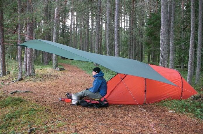 ヒルバーグのタープとテントで休む男性