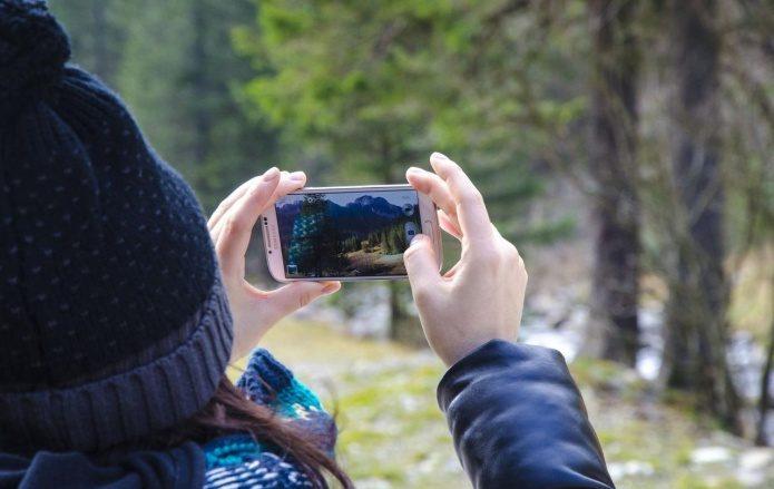 大容量モバイルバッテリーで充電して景色を撮影する女性