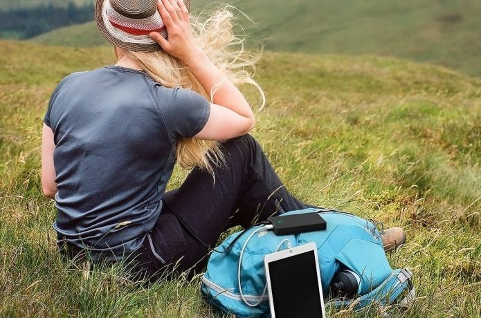 大容量モバイルバッテリーで充電する女性
