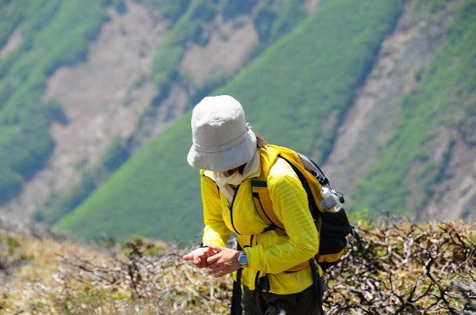 アウトドアの帽子をかぶって登山中の女性