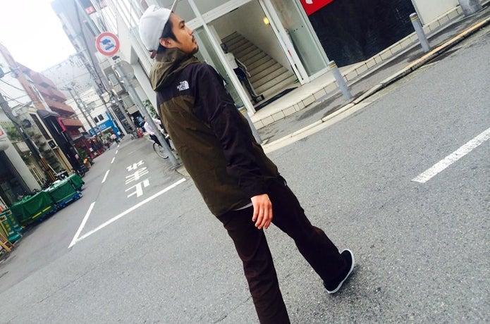 マウンテンパーカーのブランドものを着て歩く男性