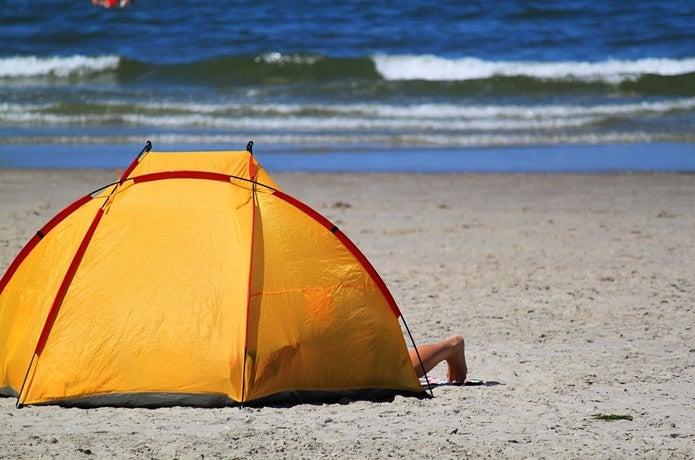 ビーチでサンシェードテントを立てる
