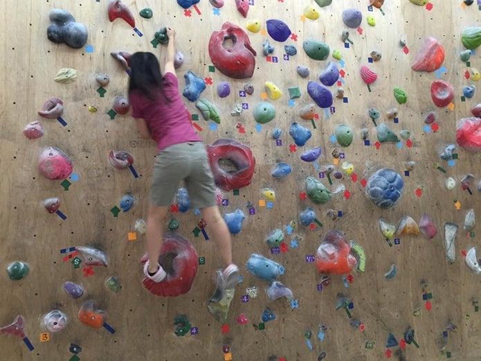 ボルダリングホールドを使って登る女性
