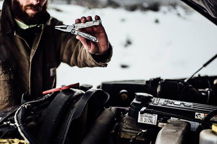 レザーマンのツールを使う男性