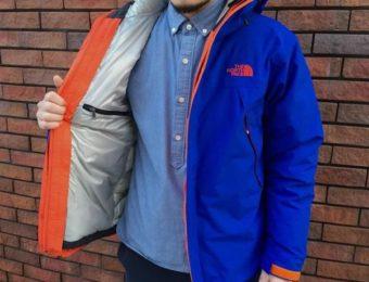 ノースフェイスのスクープジャケットを羽織る人