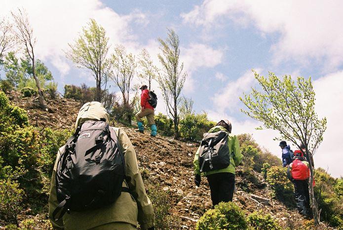 モンベルのバックパックを背負って山を登る人