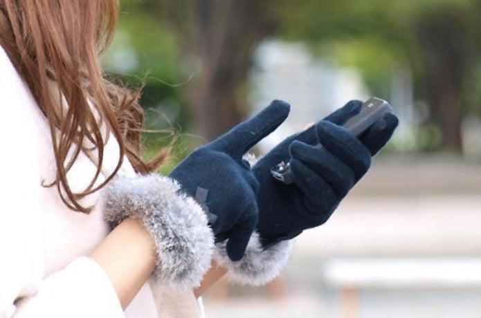 手袋をつけたままスマホを操作する女性