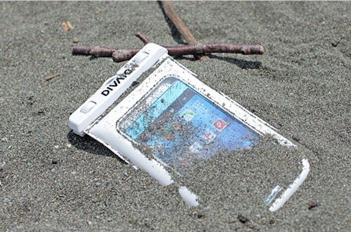 防水スマホケースを砂に埋める