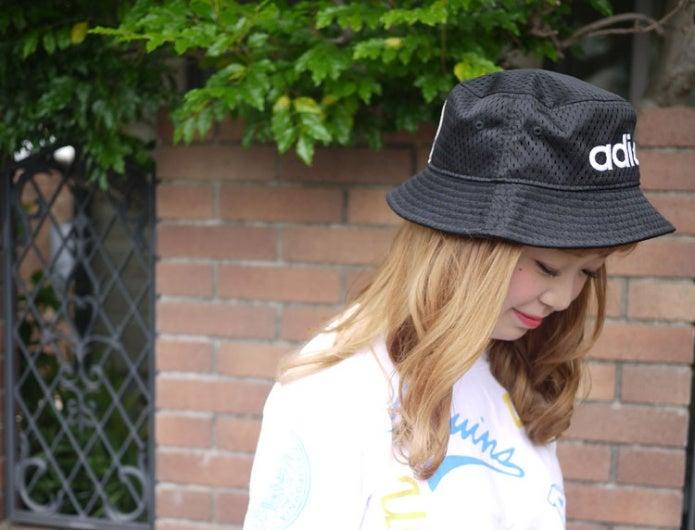 アディダスの帽子をかぶる女性