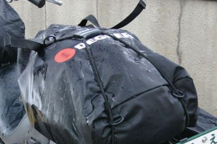 バイクに荷積みされた防水リュック