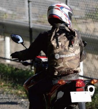 防水リュックを背負いバイクに乗る男性