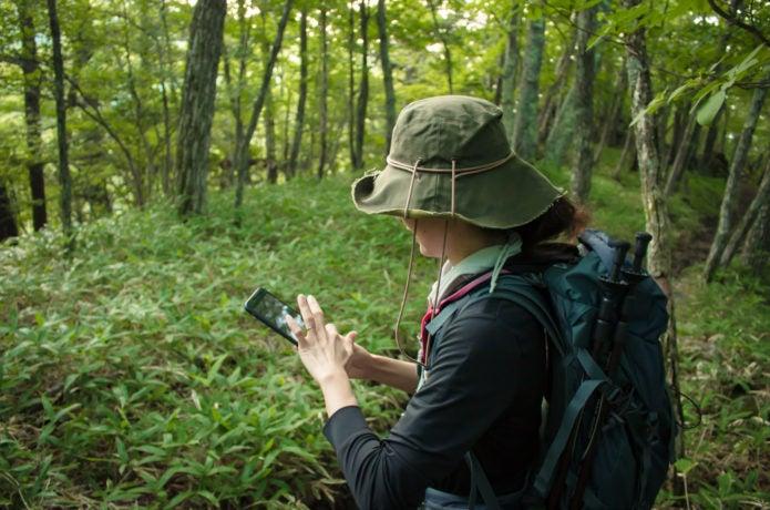 登山地図アプリを使う女性