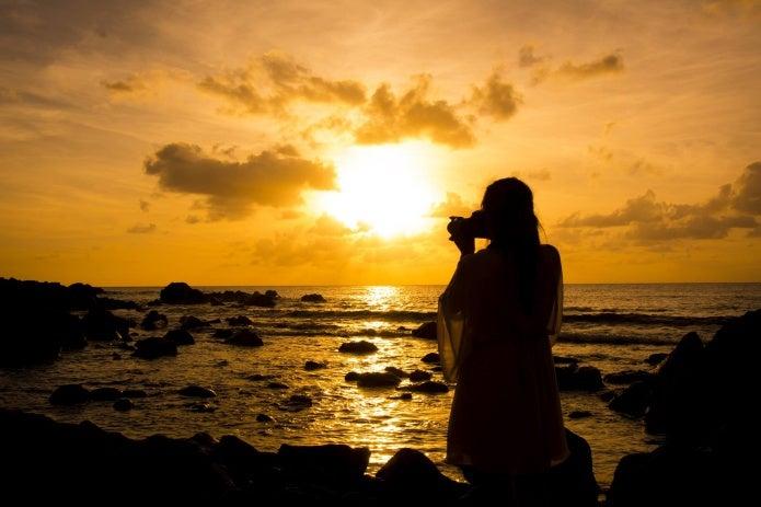 夕焼けを撮影する女性