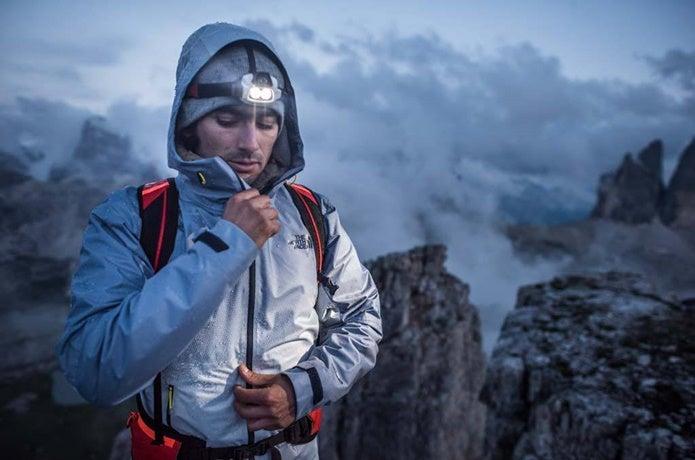 レインウェアを着て登山する男性