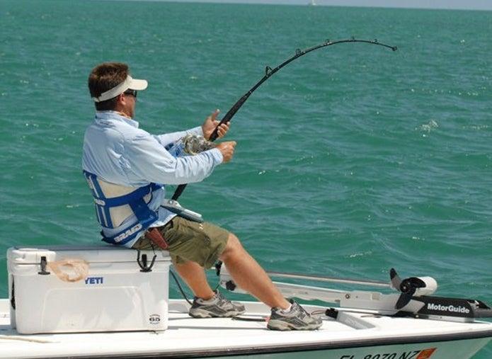 クーラーボックスに座って釣りをする人