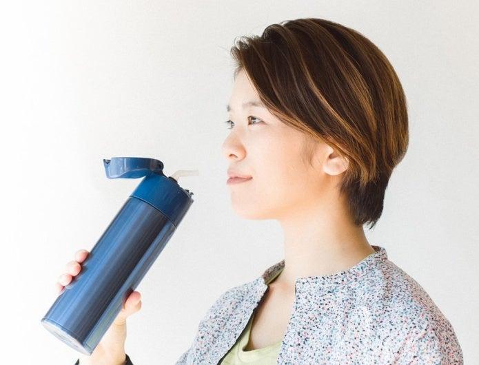ストロー付きの水筒を使う女性