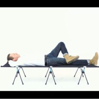 アウトドアベッドで横になる人
