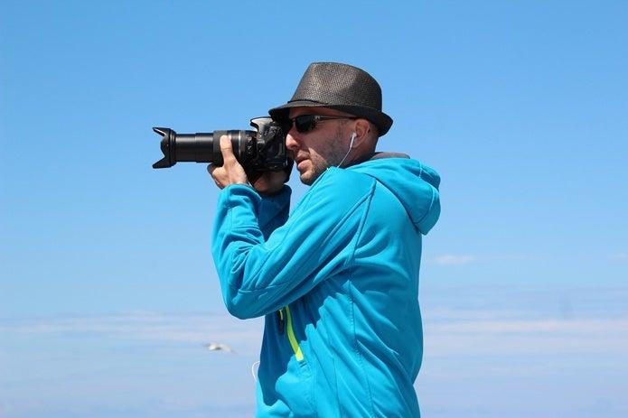 望遠レンズで撮影する男性