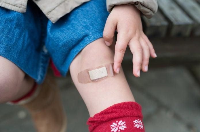 救急セットを使って絆創膏を貼った子供