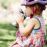 ストロー付きの水筒を使う子供