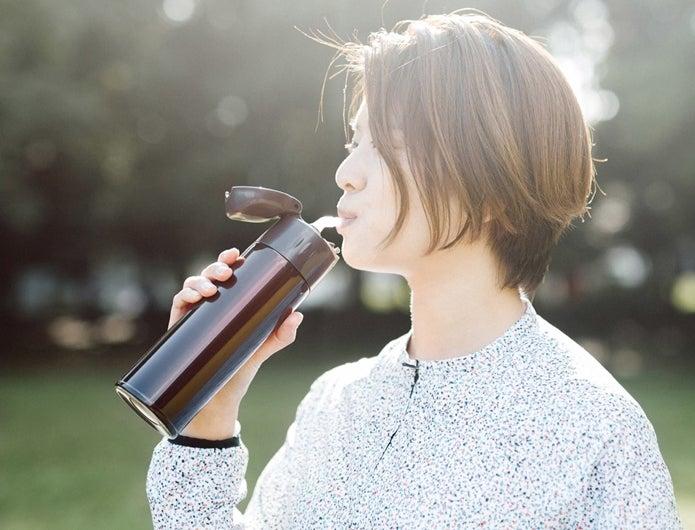 ストロー付きの水筒で水分を摂る女性