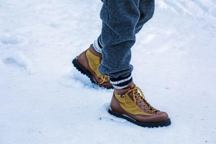 雪の中を歩く男性の足