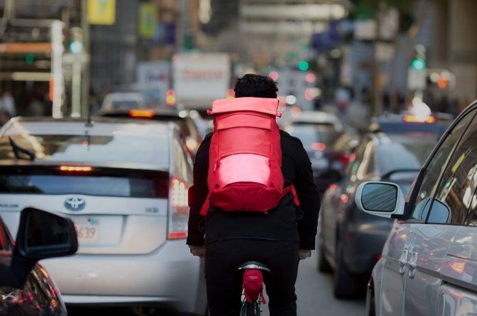 ティンバック2の赤いリュックを背負って自転車に乗る男性