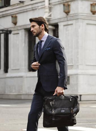 スーツを着てマンハッタンポーテージのメッセンジャーバッグを持つ男性