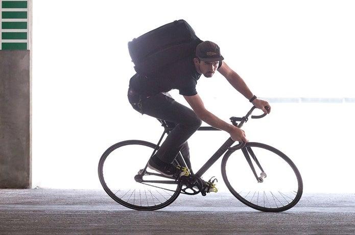 メッセンジャーバッグを背負って自転車に乗る男性
