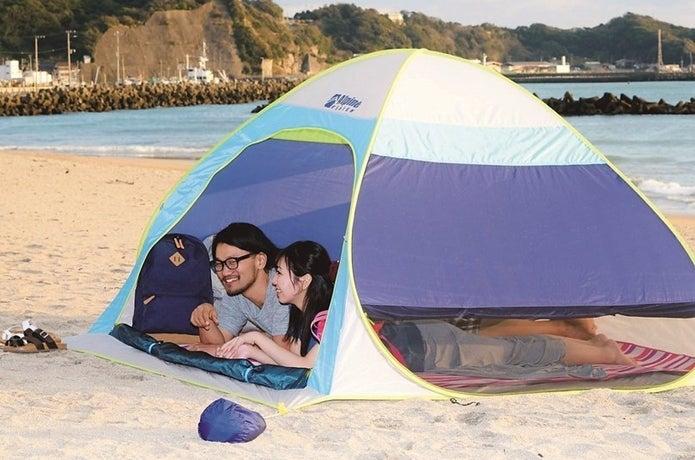 ポップアップテントをビーチで使う男女