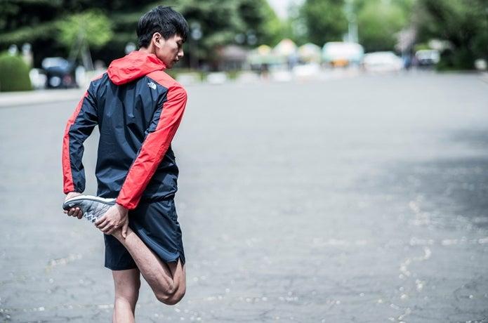 ノースフェイスのジャケットを着てストレッチする男性