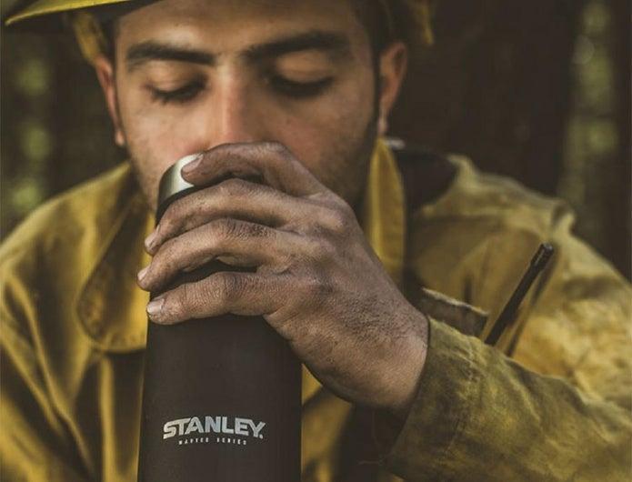 ステンレスボトルで飲み物を飲む男性