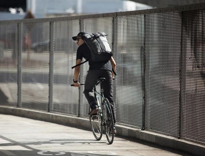バックパックを背負って自転車に乗る人