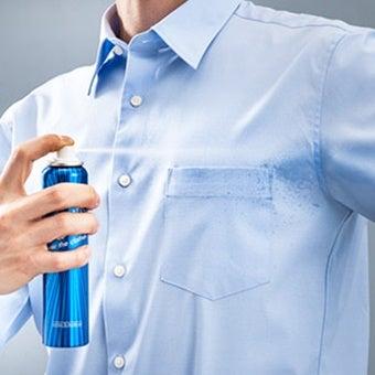 冷却スプレーでワイシャツを冷やす人