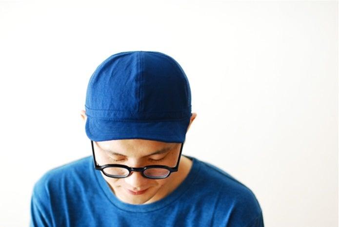 ノースフェイスの青いキャップをかぶった男性