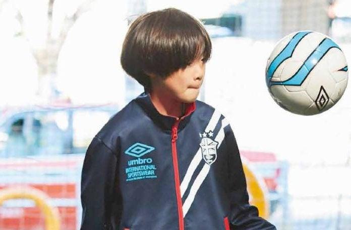 アンブロのウィンドブレーカーでサッカーをする少年