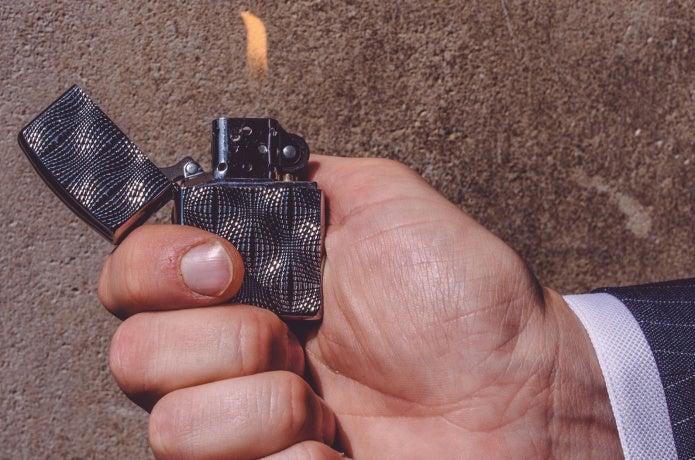 ジッポライターを持って着火している男性の手元