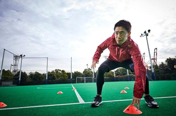 アディダスのウィンドブレーカーでトレーニングするサッカー選手
