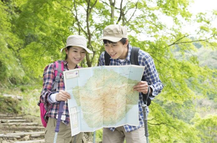 登山で地図読みをする男女