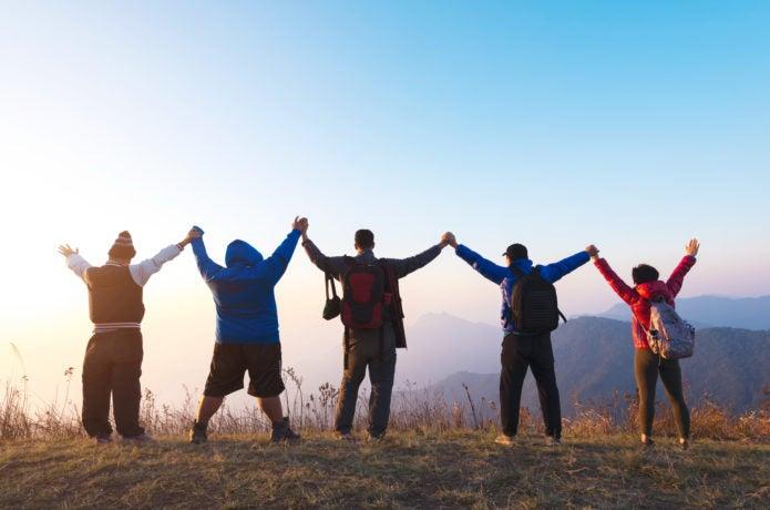 山で万歳をする人々