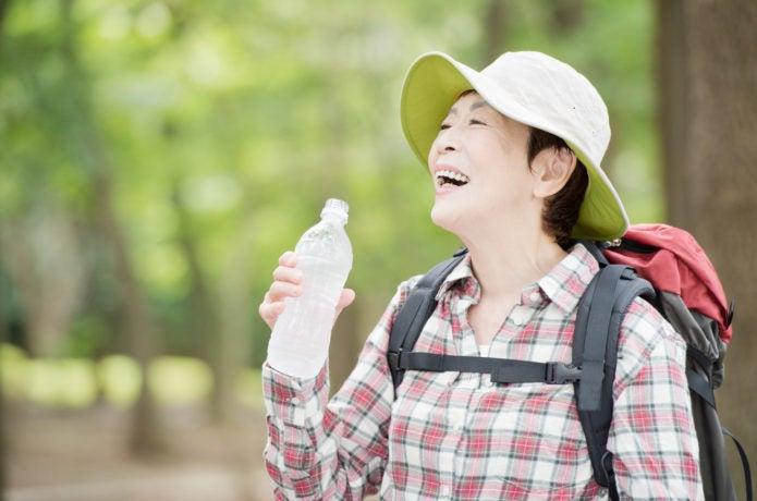 登山中に飲み物を飲む女性