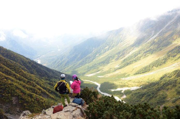 ヘルメットをかぶって登山する男女