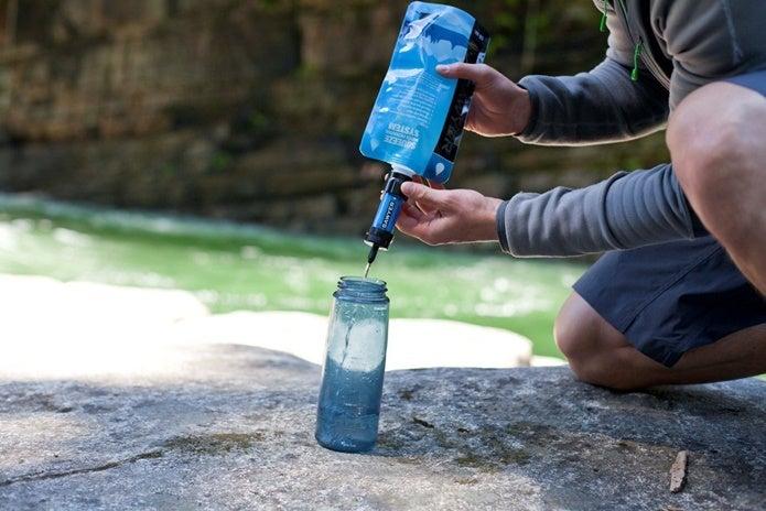 ボトルにソーヤーミニで浄化した水をためる人
