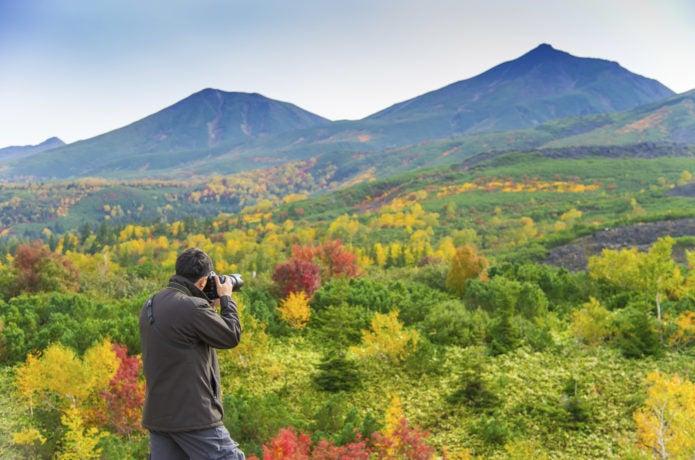 十勝岳の紅葉を撮影するカメラマン