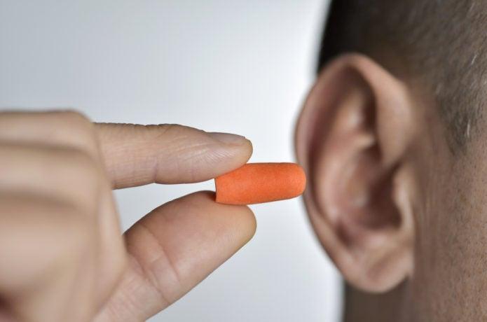 耳栓を付けようとしている画像